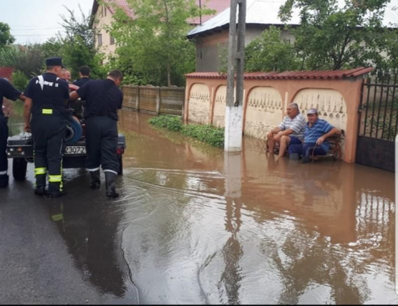 Fotografia zilei vine din Teleorman: doi localnici stau pe bancă în timp ce pompierii scot apa din comună