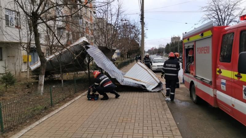 Mașini avariate de un acoperiș smuls de vânt, pe Calea Națională