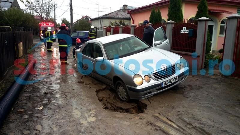 Stradă din municipiul Botoșani surpată din cauza precipitațiilor! Mașina unui fost viceprimar a rămas blocată intr-o groapă! FOTO